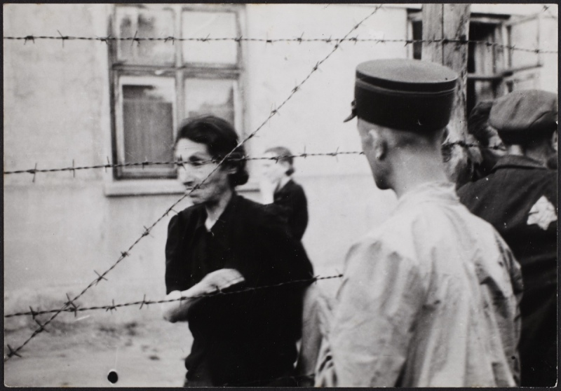 Lodz ghetto: Ghetto police with woman behind barbed wire 	Henryk Ross (Polish, born in 1910-1991) 		1942 	Gelatin silver print. 	*Art Gallery of Ontario. Gift from the Archive of Modern Conflict, 2007. 	*© Art Gallery of Ontario 	*Courtesy Museum of Fine Arts, Boston 		*Reproduced with permission
