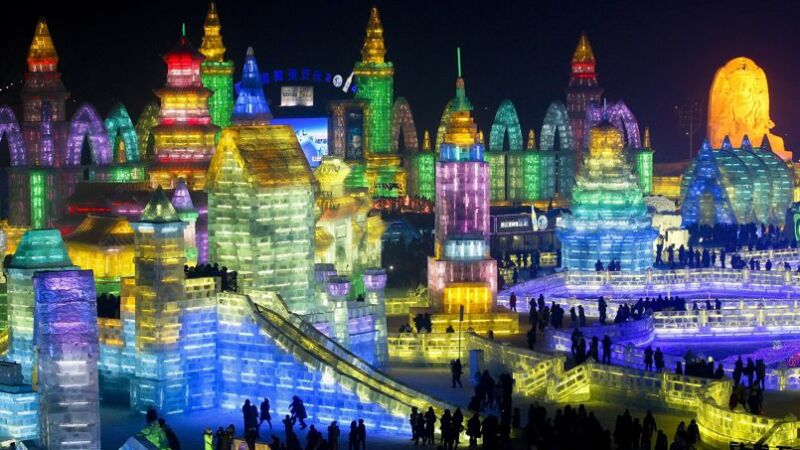 Visitors tour colorful ice structures during the opening ceremony of the Harbin International Ice and Snow festival in Harbin, in northeastern's China's Heilongjiang province, Sunday, Jan. 5, 2014. (AP Photo) CHINA OUT
