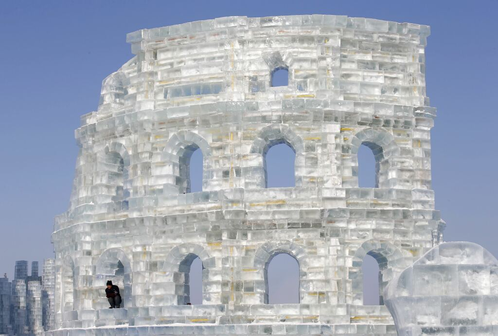 A worker takes a rest while giving the last touches to an ice replica of Rome's Colosseum in Harbin