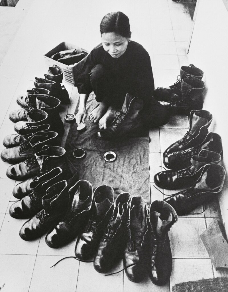 ca. 1973, Vietnam --- Vietnamese woman shining military boots during the departure of American troops. --- Image by © Christine Spengler/Sygma/Corbis