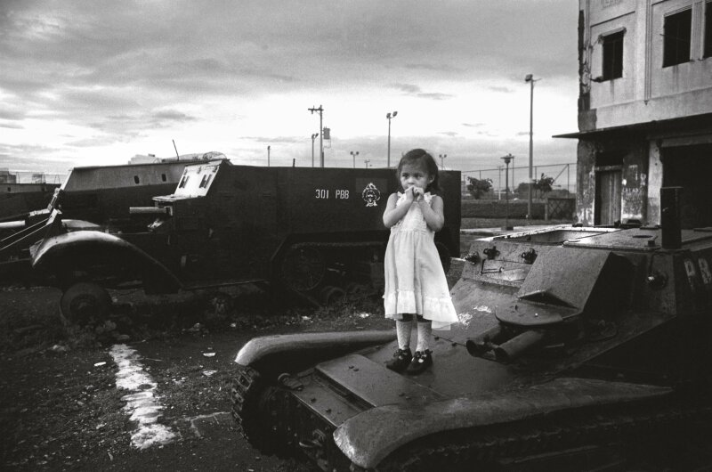 01 Nov 1980, Managua, Nicaragua --- A young girl stands on a tank parked in Louis Alfonso Velasquez Park in Managua, Nicaragua. Nicaragua plunged into civil war after the Sandinistas took over the government in 1979. --- Image by © Christine Spengler/Sygma/Corbis
