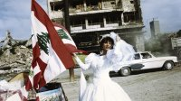 1996, Beirut, Lebanon --- A Lebanese bride poses next to the flag of Lebanon on a street in Beirut. Life appears to go on amid the destruction five years after the end of the civil war that ravaged the country and left it a political, economic, and physical shambles. --- Image by © Christine Spengler/Sygma/Corbis