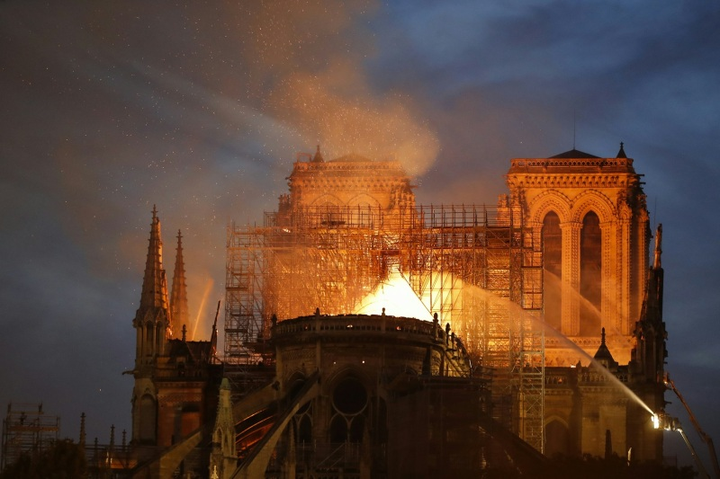 Firefighter douse flames billowing from the roof at Notre-Dame Cathedral in Paris on April 15, 2019. - A major fire broke out at the landmark Notre-Dame Cathedral in central Paris sending flames and huge clouds of grey smoke billowing into the sky, the fire service said. The flames and smoke plumed from the spire and roof of the gothic cathedral, visited by millions of people a year, where renovations are currently underway. (Photo by FRANCOIS GUILLOT / AFP)