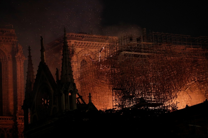 Flames are seen through the scaffolding as they engulf the roof of the Notre-Dame Cathedral in Paris on April 15, 2019. - A fire broke out at the landmark Notre-Dame Cathedral in central Paris, potentially involving renovation works being carried out at the site, the fire service said. (Photo by Geoffroy VAN DER HASSELT / AFP)