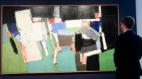 """A man looks at the 1952's painting oil on canvas  """" Parc des Princes """"  by Nicolas De Stael at the Christie's France during the FIAC (International Fair of Contemporary Art)exhibition, in Paris, on October 16, 2019.     gathering in front of the Ministry of Health in front of Ministry of Health october 8, 2019 in Paris. AFP PHOTO / BERTRAND GUAY Estimated between 18 and 25 million euros, this painting was the largest work of the Russian artist, the painting will be auctioned on October 17, 2019. © AFP / BERTRAND GUAY"""