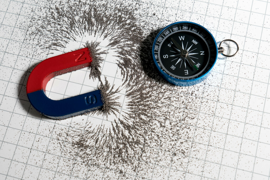 Red and blue horseshoe magnet or physics magnetic and compass with iron powder magnetic field on white paper graph background.