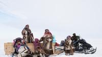 Une famille portant les vêtements traditionnels pour un après-midi dans la toundra.