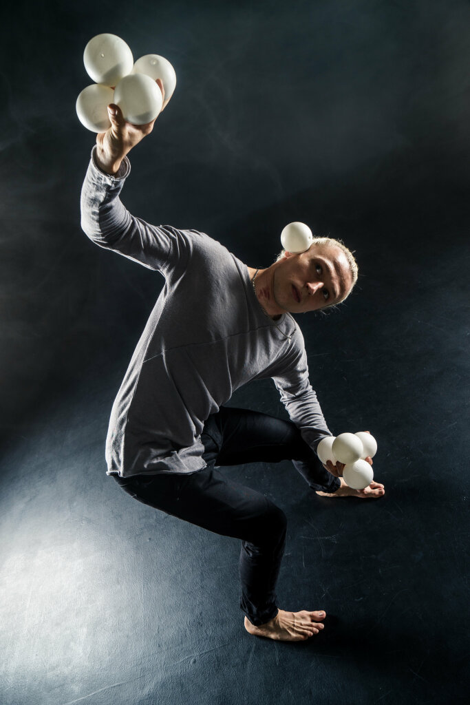 Blond juggler with white balls on black background