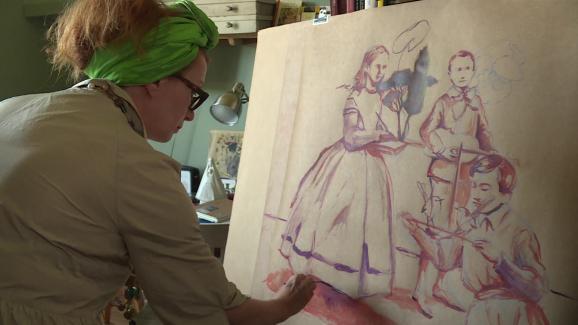 """Nathalie Novi, l'iniatrice du projet de fresque collective, en train de peindre sa """"famille confinée"""", dans son atelier du Jura."""