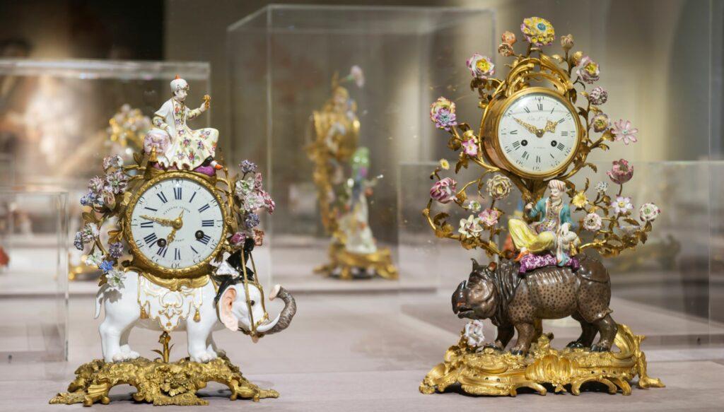 Exposition Meissen folies de porcelaine au musée Ariana- Agauche Penduleavecéléphant,vers1745 et AdroitePenduledecheminée, ModèledeJohannJoachimKändler,vers1750‐55