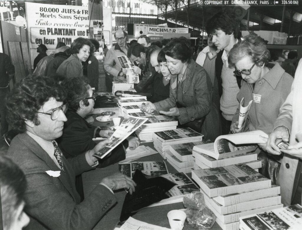 Photographie de Serge Klarsfeld dédicaçant son ouvrage. 1978