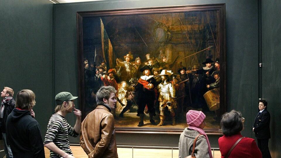 Les visiteurs du Rijksmuseum d'Amsterdam devant La Ronde de nuit de Rembrandt