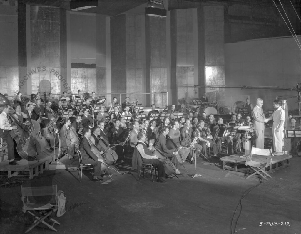 Charles Chaplin and Alfred Newman directing the orchestra, 1925