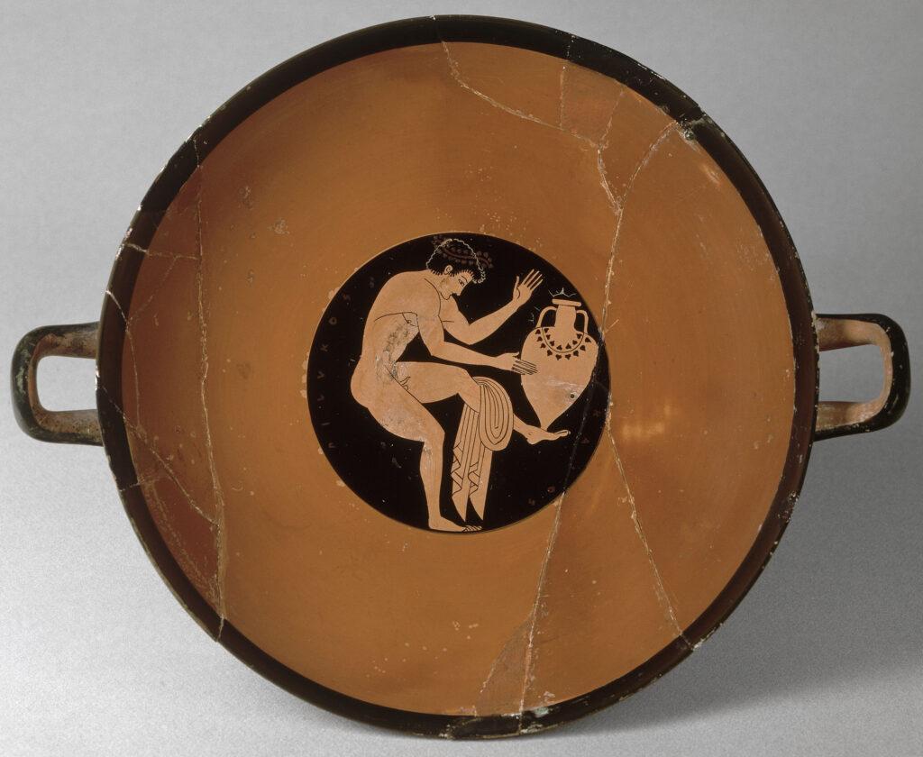 Coupe à figure rouge comaste jouant à faire tenir une amphore sur son pied, 510-500 av. J-C
