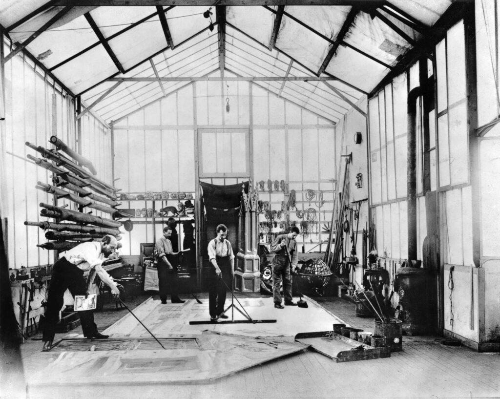 Georges Méliès, à gauche, dans le Studio A peignant un décor au sol, vers 1900