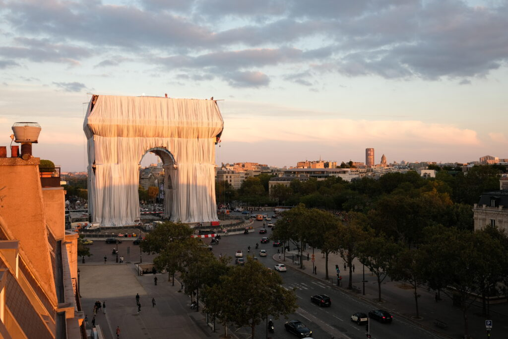 Fabric panels are being unfurled in front of the outer walls of the Arc de Triomphe