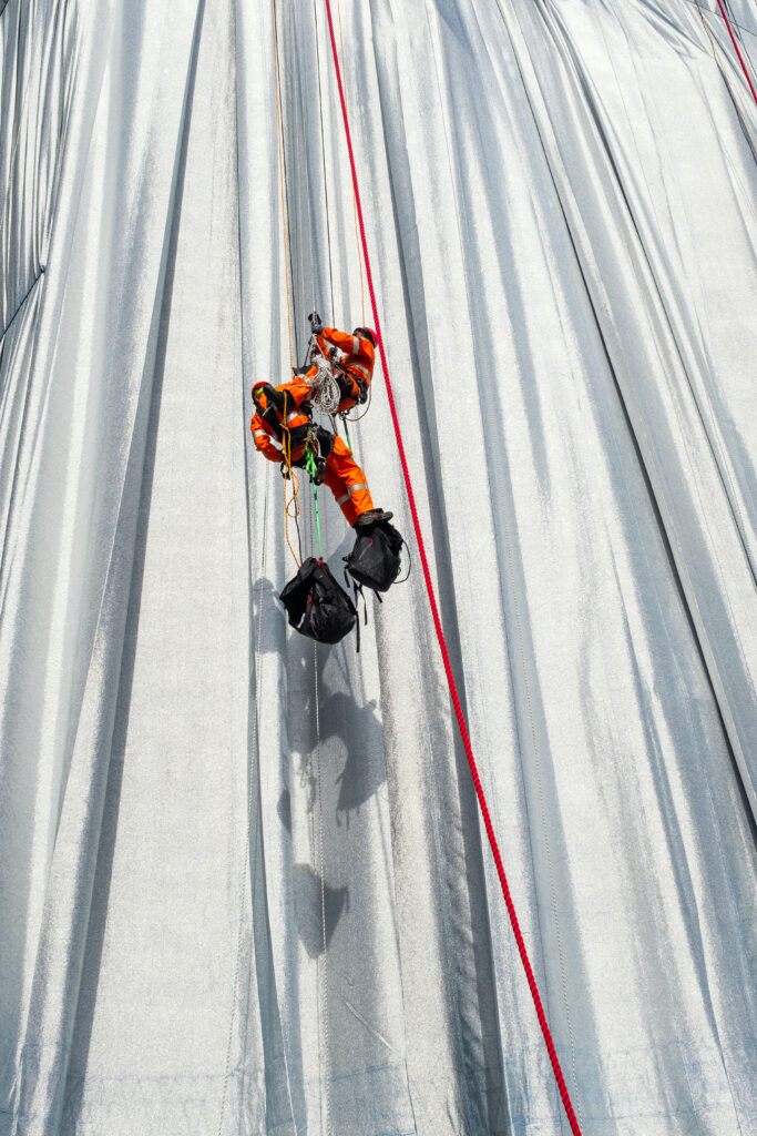 Ropes are being installed to secure and contour the fabric on the Arc de Triomphe