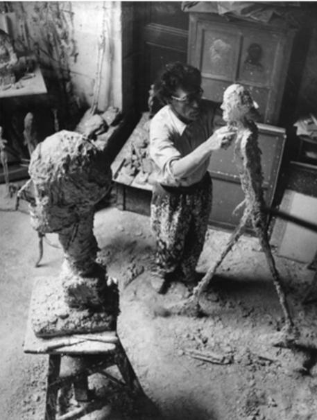 A. Giacometti travaillant au plâtre de l'Homme qui marche, dans l'atelier, 1959