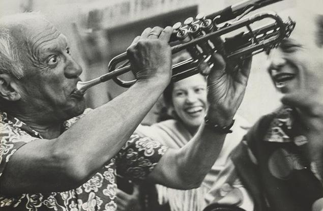Pablo Picasso jouant de la trompette dans la rue de Vallauris, le 4 août 1954